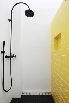 Achromatic colour scheme with a pop of yellow in bathroom for a sense of energy and excitement to the space. With the addition of matte black shower rose for a sophisticated finish. Designed by Woods and Warner, Sydney @woodswarner