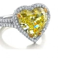 Heart Shape Fancy Yellow Diamond Engagement Ring - One of the most stunning pieces comes this Heart Shape Fancy Yellow Diamond Engagement Ring that features a Heart Shaped Yellow gemstone in a prong setting. Stamped in 14k White with halo style White Round cut accent stones on the double shank & center stone. This Fancy Yellow Heart ring comes with a VS & VS2 in clarity & an F in color & the total gem weight is equal to 2.51 carats. All of the diamonds are 100% natural…