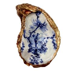 "This signature oyster shell dish features a blue and white Chinoiserie design. This is a traditional Chinese scene.  We carefully apply the gold gilding to the edges by hand. Each dish is unique. We use the very largest oyster shells that measure 3""-5"" in length.   The oyster shell dishes are perfect to hold bracelets, earrings, rings, small candy, stamps, and all kinds of trinkets.  The signature oyster shell dish is packaged in a white gift box."