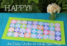 Hi again! I'm Jen Daly and I'm back at the Moda Bake Shop today with a great mini charm pack project that's perfect for summer. Happy!! is a 13″ x 25 1/2″ table runner that features a garden of cheerf