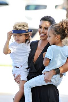 Kim Kardashian, wearing a low cut, silk maxi dress, holds on tight to nephew Mason and his pal Sophia as they and Kourtney head out for an afternoon of filming