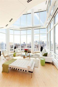 buntes Innendesign modern Eleganz weiß grün Glastisch Holzboden