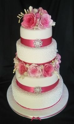 4 tier wedding cake blocked with hand made sugar roses and freesia, and finished with cornelli piping, ribbon and brooches