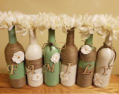 Painted wine bottle set with one letter per bottle to spell out Family when all placed together. The colors are sage green and ivory with twine and flower decor. These look great on a shelf or window ledge. Alcohol Bottle Crafts, Glass Bottle Crafts, Wine Bottle Art, Painted Wine Bottles, Diy Bottle, Mason Jar Crafts, Mason Jar Diy, Wrapped Wine Bottles, Twine Wine Bottles