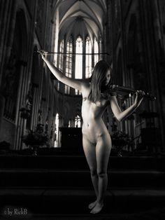 ragazza nuda suona il violino in una chiesa