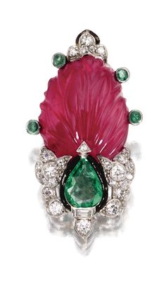 CARVED RUBY, EMERALD AND DIAMOND PIN, CARTIER, PARIS, CIRCA 1930 The stylized topiary motif set with a carved ruby leaf, a pear-shaped emerald and small round and single-cut diamonds, accented further with 4 small cabochon emeralds and black enamel, mounted in platinum, signed Cartier, numbered 2432, French assay mark.