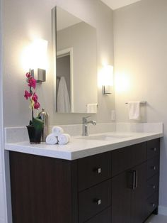 HGTV presents a dark brown bath vanity with quartz countertop that features a mirrored medicine cabinet and sleek chrome wall sconces.