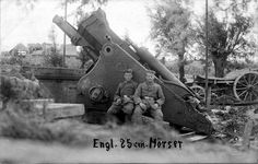 Two German soldiers pose against a destroyed 25cm British gun.