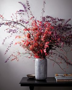 Chrysanthemum Arrangement -  Gather armfuls of vivid leaves and berries from the garden before the snow gets them. Ordinary chrysanthemums can look stiff when arranged on their own. But nestled in a fountain of red winterberry, burning bush, and purple beauty-berry, they are dramatic and unexpected.