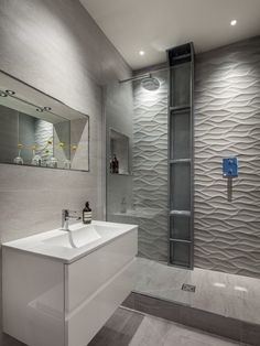 carrelage mural grand format 3D en gris comme accent dans la petite salle de bains