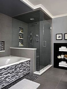 Sheathed in oversize ceramic tile the shower is grounded with a textured river rock floor. A rain-style showerhead and handheld wand enhance showering. The same linear tile on the vanity backsplash covers the tub surround and niche adding a third layer of tile style.