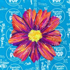 Red/Orange flower created with recycled candy and drink labels on a Blue Raspberry Tootsie Pop Wrapper. #recycledart #recycledmaterial #reuse #reclaim #TootsiePop