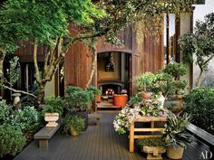 On the terrace of designer Ken Fulk's home in San Francisco, flowering dogwood branches spill across an antique Japanese worktable partially shaded by a grove of Japanese maples in the Zen-inspired garden. The benches and deck are redwood, which is also used on the house's façade   archdigest.com