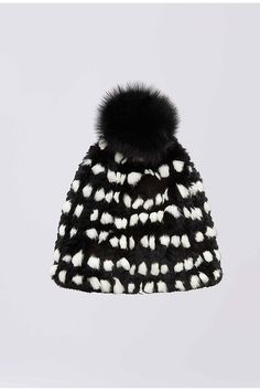 A comfortable rabbit fur hat in a modern black and white print and a festive pom pom.