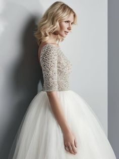 Sottero and Midgley - ALLEN, This show-stopping ballgown features a sheer bodice of Swarovski crystals and beading atop a voluminous tulle skirt. Complete with half-sleeves, an elegant illusion bateau over sweetheart neckline, and sexy open back. Finished with crystal buttons over zipper closure.