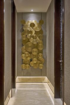 Contemporary gold wall sculpture focal point in hallway |