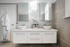 White vanity with chrome handles, twin white round basins, chrome tap and mixer, dual mirror, grey tiled walls. Visit our website for more . Modern Vintage Bathroom, Modern Farmhouse Bathroom, Classic Bathroom, Modern Bathrooms, Bathroom Decor Pictures, Diy Bathroom Decor, Light Bathroom, Bathroom Ideas, Bathroom Makeovers On A Budget