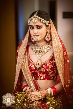 Beautiful bridal portrait in stunning jewellery and a red lehenga |WedMeGood| Sahil & Kritika|#wedmegood #indianweddings #redlehenga #bridallehenga #goldwork #red #lehenga #bridal #blouse #bridalbun #jewellery #bridaljewellery #nosering
