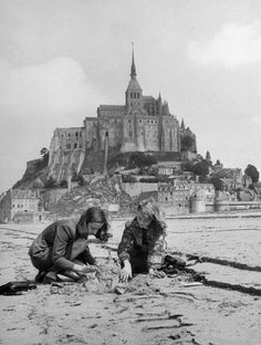 Yale Joel - American travelers building a sand replica of France's medieval abbey at Mont-Saint-Michel in the background, July 1948.