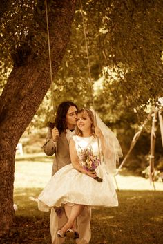 Kiss on the cheek by the groom while the bride sits on a tree swing.  Copyright Photographics Solution 2012
