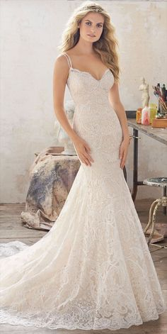 Romantic Wedding Dress Featuring Beautiful Allover Embroidered Lace on Net with Crystal Beaded Double Straps and Scalloped Hemline. Open Back Accented with Scalloped Lace Detail and Covered Buttons.