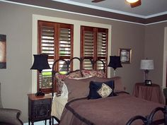 Master Bedroom where Window Fashions of Texas installed stained shutters on windows with white casements.
