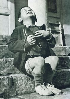 "Austrian boy receiving new shoes after WWII. ""New Shoes"" by Gerald Waller, Austria Six year-old Werfel, living in an orphanage in Austria, hugs a new pair of shoes given to him by the American Red Cross. This photo was published by Life magazine."