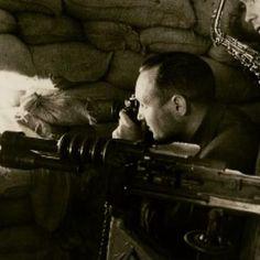 Spain - 1936. - GC - Este fotografo y este musico no pueden evitar asomar la cabeza por la tronera del nido de ametralladora. La maquina una hotchkiss muy presente en los frentes durante la guerra civil.