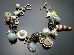 "Susan Chin    Charm bracelet H: sterling silver, steel, 18ky gold, glass eyes, aventurine, bone, pink ivorywood, freshwater pearls, rainbow moonstone, jasper, etc. Length 7.5""."