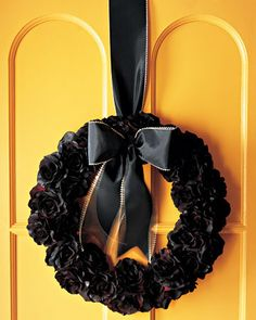 This fall floral wreath -- inspired by Halloween -- is made with silk roses, sprayed in black paint, and decorated with a silky taffeta ribbon.