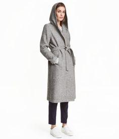 Graumeliert. Langer Bouclé-Mantel aus Wollmischung. Der Mantel hat eine gefütterte Kapuze, Seitentaschen…