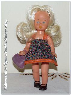 Κούκλα ελληνικής κατασκευής από την δεκαετία του 1960's. Είναι φτιαγμένη από άριστης ποιότητας βινύλιο και η κατάσταση της είναι πολύ καλή. Η κούκλα είναι μίνι σε μέγεθος με ύψος 18εκ. Φοράει πολύ όμορφο τιραντέ φόρεμα με φουφούλα, παπούτσια και τσαντάκι από καρτέλα παιχνιδιών τις εποχής εκείνης.