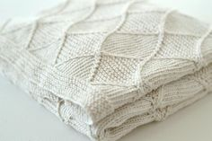 Rocket Clothing London by Linda Whaley. This diamond cable and garter stitch blanket is a beautiful blanket for a baby boy or baby girl as it looks…