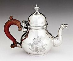 A Britannia standard silver teapot, Paul de Lamerie, London 1719 of baluster form, the hinged dome cover, wooden handle and ribbed spout with armorials to front and reverse
