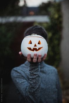 Hand holding white painted jack o lantern by Ruth Black