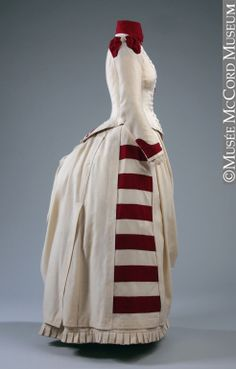 White/cream wool dress with dark red accenting stripes, by J. J. Milloy, 1887. Side view.
