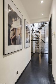 A corridor lined with fashion photographs and a dramatic spiral staircase lead to two luxu...