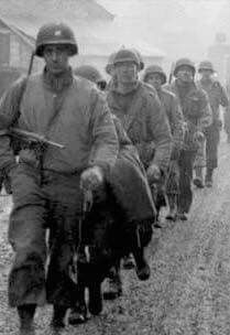 Battle of the Bulge! Soldiers of the 28th Infantry Division march down a street in Bastogne,Beligum, December 20, 1944.