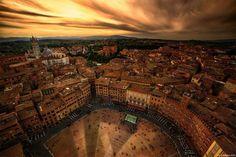 Siena é uma das mais fascinantes cidades de Itália. Está situada na região da Toscana e é uma das cidades mais populares da Itália medieval. Devido à sua história, foi declarado Património Mundial da UNESCO e é um dos locais favoritos para turistas. Aqui, nesta imagem, vemos a praça principal, em forma de meia-lua: é …