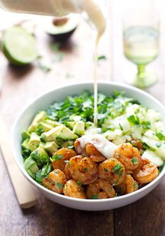 Spicy Shrimp and Avocado Salad with cucumbers, baby kale, shrimp, and avocado, with creamy miso dressing.