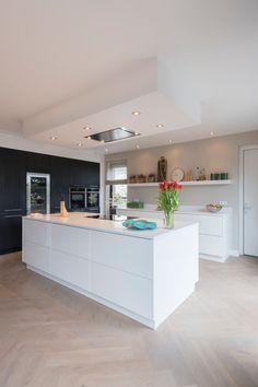De moderne, strakke keuken heeft een fijn contrast van kleur en materialen: wit hoogglans en zwarte houtnerven. De keuken is weliswaar modern, maar oogt heel gezellig. Dat komt onder meer doordat het afzuigsysteem in een verlaagd plafond is aangebracht, de nis ruimte biedt aan onder meer kookboeken en de houten accessoires in het oog springen op de wandplank.  Kitchen Interior, New Kitchen, Home Interior Design, Kitchen Decor, Black Kitchens, Luxury Kitchens, Home Kitchens, Kitchen Remodel Pictures, Kitchen Diner Extension