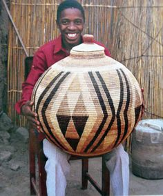 "Africa | ""Lejahe Tembo of Gomare, Botswana, with a coiled basket made from palm fiber""  