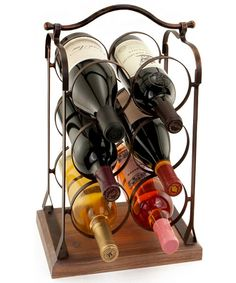 "Six Bottle Wine Rack from WineRacks.com  The Six Bottle Wine Rack will make for a great wine and decor accessory. It's the perfect accent piece by the bar or dining table. The Six Bottle Wine Rack has a rustic feel with weathered wood treated base and brass-like antiqued body and handle. For an excellent upsell opportunity, this wine rack matches nicely with our Wood Wine Bottle and Cork Holder, Wood Carrier and Wood Tray for a coordinated decor look.  Dimensions: 10 3/4"" x 16 3/4"" x 7 1/2"""