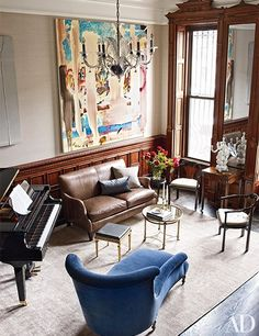 In the music room, walls clad in a Donghia fabric serve as a backdrop for a large Annie Lapin painting, which overlooks a Yamaha player piano and a Bourgeois Bohème Atelier chaise longue.