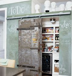 Beautiful vintage door covering hidden wine refrigerator and other kitchen items.  Plus beautiful green aged chalk board paint on surrounding walls.