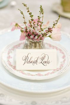 Pretty place setting with vintage themed plates, beautiful mini floral arrangement, and a handwritten place card #wedding #vintage #vintagewedding #placesetting #pink