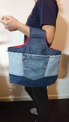 This tote bag is completely handmade and each piece is unique. It is made with recycled denim and lined with a red cotton fabric. A central pocket denim is applied on each side. Ideal for home storage or for shopping, it is reinforced for extra support. Dimension: height 45 x 40 cm width