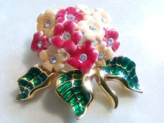 HIGH END COSTUME JEWELRY. SIGNED DESIGNER COSTUME JEWELRY. JOAN RIVERS BROOCH/PIN/ACCESSORY. MINT VINTAGE. From the unforgettable, phenomenal, Joan Rivers, jewel2jewel brings you this superb, very fine quality, brooch. Gorgeous, very chic, floral motif pin/accessory. The jewel is crafted with shining, very rich, pink, cream and green enamel. The gold gilt glistens and shines. The lovely flower bouquet is a treasure. The flowers have sparkling clear faceted crystal centers. All of this…
