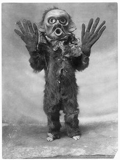 """Koskimo person wearing full-body fur garment, oversized gloves and mask of Hami (""""dangerous thing"""") during the numhlim ceremony.:"""