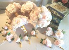 Bouquets are made in blush handmade filter paper Peonies and Roses with gold baby's breath. The handles on the small bridesmaid bouquets are wrapped in light gold ribbon and sparkling gold rhinestone ribbon and the medium size bridal bouquet is wrapped in white satin ribbon and lace with an organza flower and brooch.